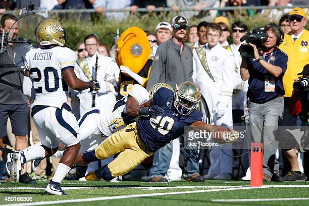 J Prosise of the Notre Dame Fighting Irish dives into the end zone for a 17yard touchdown against the Georgia Tech Yellow Jackets in the second...