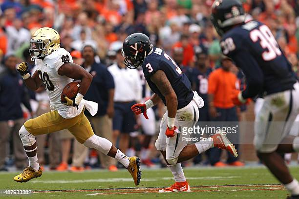 J Prosise of the Notre Dame Fighting Irish rushes past safety Quin Blanding of the Virginia Cavaliers for a touchdown in the third quarter at Scott...