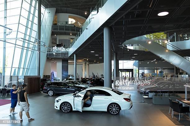 Prospective buyer inspecting a Mercedes CLA 180 Saloon in MercedesBenz showroom in Stuttgart Bavaria Germany