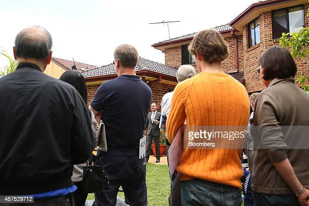 Prospective buyers and onlookers listen during an auction of a property in the suburb of Roseville Sydney Australia on Saturday Oct 18 2014 Sydneys...