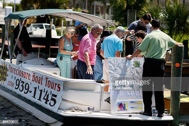 Prospective buyers exit from their boat as they prepare to inspect a home that is part of the foreclosure boat tour by Foreclosures 'R Us realty...