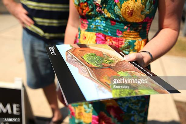 Prospective buyers stand with a brochure during an open house inspection at a property in the suburb of Willoughby in Sydney Australia on Saturday...