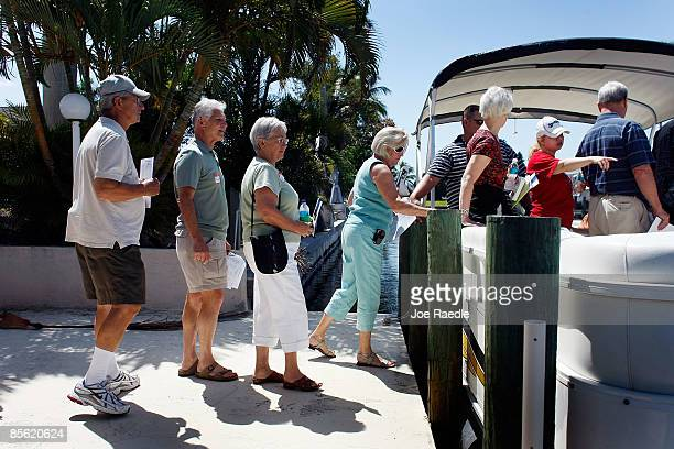 Prospective buyers walk onto a boat as they prepare to inspect homes that are part of the foreclosure boat tour by Foreclosures 'R Us realty company...