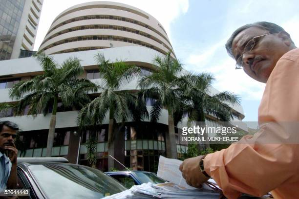A prospective investor leafs through subscription forms of companies coming out with share offers displayed outside the Bombay Stock Exchange in...