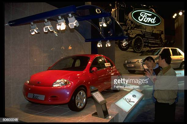 Prospective motorist checking out Ford auto display at Family Car Show featuring ka Fiesta models