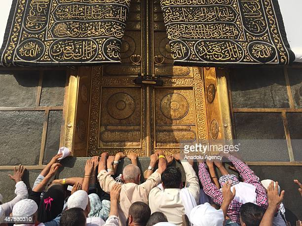 Prospective Muslim pilgrims touch the wall of the Kaaba as they circle the Kaaba at Masjid alHaram in Mecca Saudi Arabia on September 10 2015