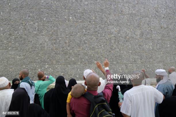 Prospective pilgrims stone a facade of Jamarat pillars that symbolize the devil as a part of the annual Islamic Hajj pilgrimage during the first day...