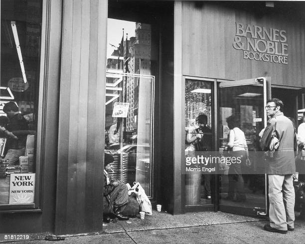 Prospective shoppers walk past a homeless man seated on the sidewalk and into a Barnes and Noble book store, New York, New York, 1980.