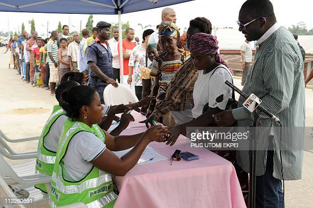 Prospective voters are accredited for the presidential election by INEC officials at Otuoke Ogbia district in Bayelsa State on April 16 2011 Nigeria...
