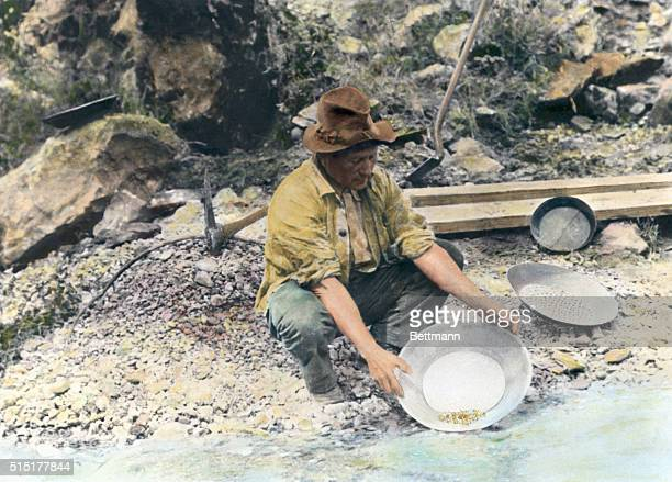 Prospector pans for gold in Northern California. Hand tinted photograph, circa 1890.