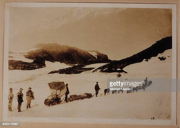 Prospectors and dog teams make their way along the trail through White Pass in British Columbia as they travel from Alaska to the Yukon Territory in...
