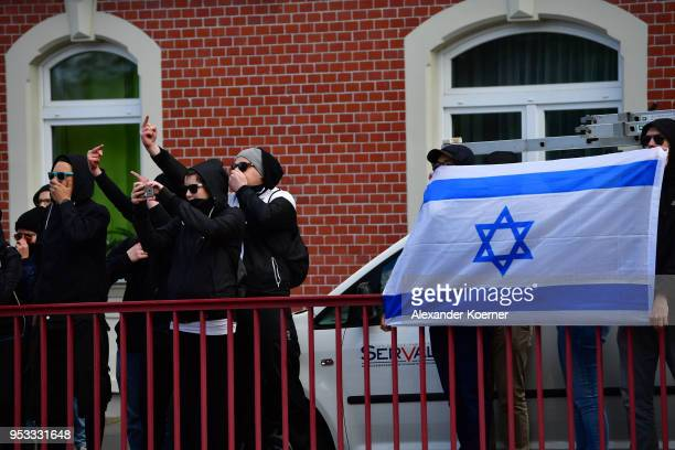 Prosters holds a flag of Jerusalem towards supporters of the farright NPD political party while gathering to march on May Day on May 1 2018 in Erfurt...