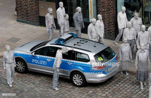 Prostestors dressedup in grey clothes like Zombies attend an arts performance called '1000 Gestalten' demonstration prior the upcoming G20 summit on...