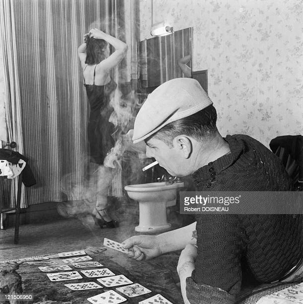 Prostitute Combing Herself While Her Man Is Playing Cards And Is Smoking