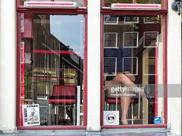 A prostitute covers her face with a cushion to avoid being photographed at her prostitution windowbooth which at the side of another for rent in the...