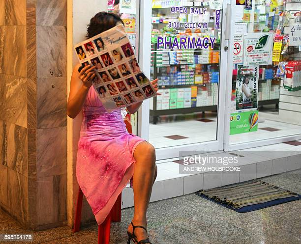 A prostitute in the Patpong area who specializes in sex for Japanese tourists hides her face from the camera The flyer she holds shows photos of the...