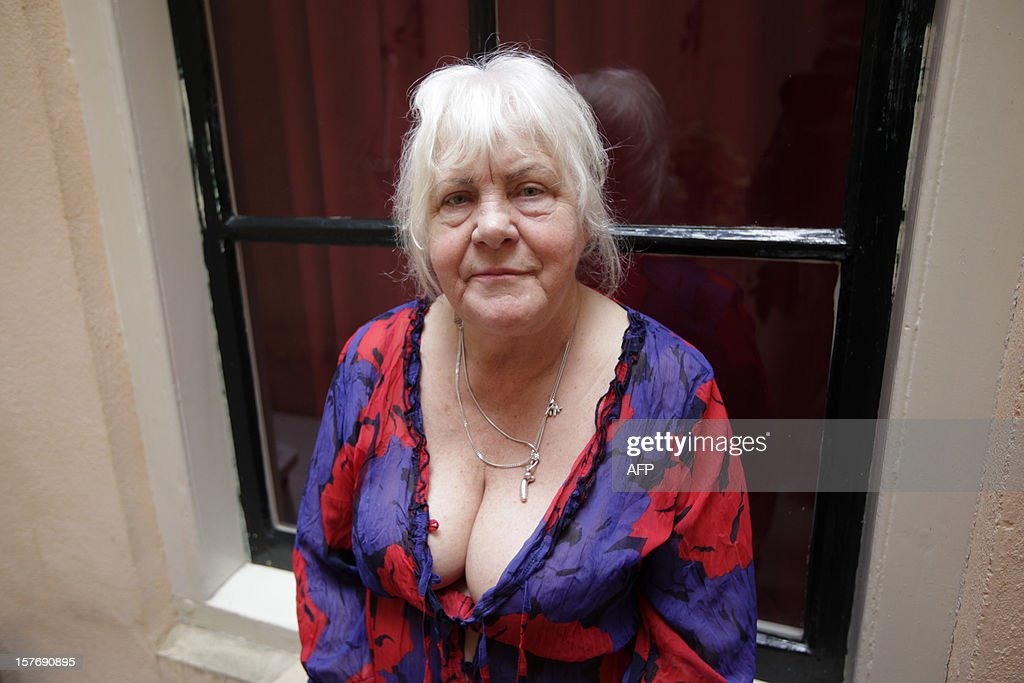 Prostitute Martine Fokkens, 70, poses for a photograph outside her apartment in the 'wallen' of Amsterdam before work on November 15, 2012, in Amsterdam, the Netherlands. Twins Martine and Louise Fokkens, nicknamed the 'Queens of the wallen', are Amsterdam's oldest prostitutes, having worked for fifty years in the city's red-light-district, and they have wrote two books about their experiences. AFP PHOTO / Anoek de Groot