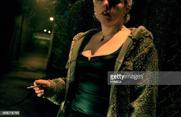 Prostitute standing in a dark street smoking a cigarette UK 1990s