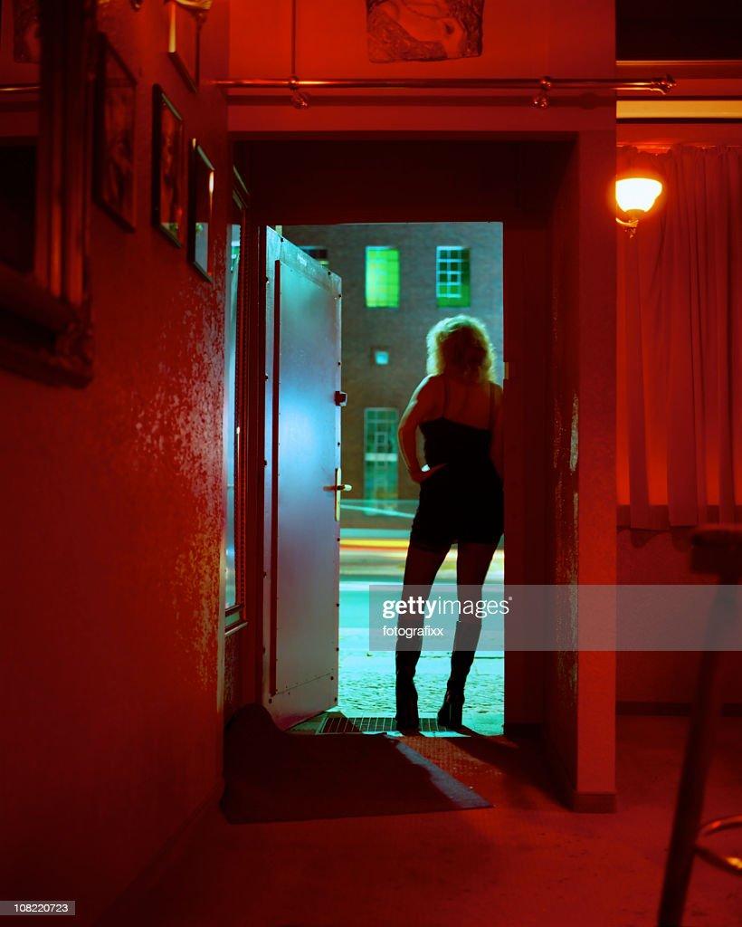 Prostituta pie en un club nocturno puerta con vista : Foto de stock