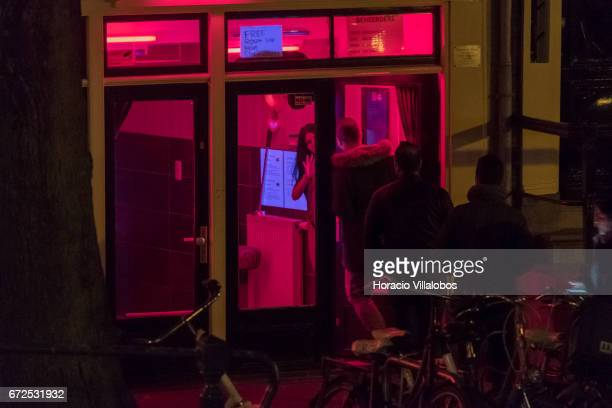 A prostitute talks to a client in the Red Light District on April 19 2017 in Amsterdam Netherlands Prostitution has been legal in the Netherlands...