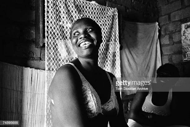 A prostitute tries to attract clients into her home at Freedom Compound near Lusaka Zambia June 2003
