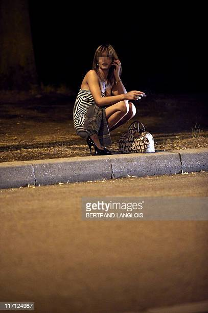 A prostitute waiting for customers sits on the sidewalk late on June 6 2011 at the Bois de Boulogne park in Paris AFP PHOTO / BERTRAND LANGLOIS