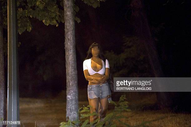 A prostitute waiting for customers stands on the sidewalk late on June 6 2011 at the Bois de Boulogne park in Paris AFP PHOTO / BERTRAND LANGLOIS