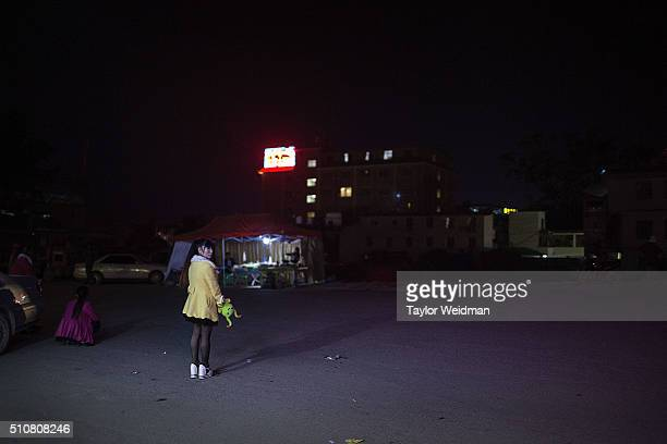 A prostitute waits for clients at an intersection on February 16 2016 in Mong La Myanmar Mong La the capital of Myanmar's Special Region No 4 is a...