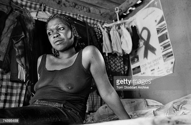 A prostitute who sells sex to truck drivers at Chirundu border crossing between Zambia and Zimbabwe February 2003 She has an HIV/AIDS poster on the...
