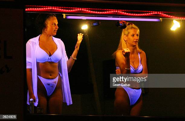 Prostitutes attempt to lure passing motorists from a brothel's display window October 21 2003 in Dubi Czech Republic Prostitution is big business...