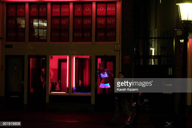 AMSTERDAM NETHERLANDS OCTOBER 30 2015 Prostitutes await for customers inside their cabins in the red light district on October 30 2015 in Amsterdam...