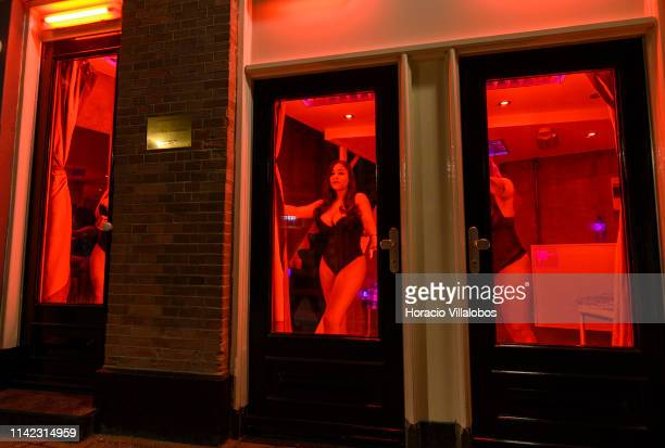 Prostitutes stand behind glass doors in the Red Light District on April 12 2019 in Amsterdam The Netherlands Amsterdam is famous for its window...