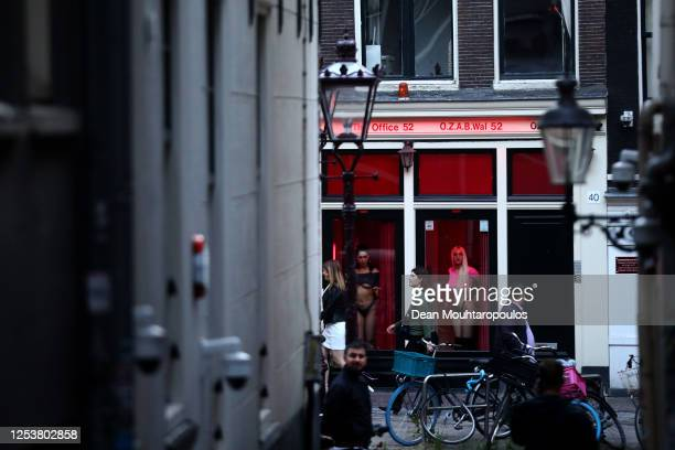Prostitutes stand behind windows in the Red Light District as it reopens after the Coronavirus or Covid19 Lockdown on July 01 2020 in Amsterdam...