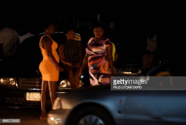 Prostitutes stand on the street in Benin City, capital of Edo State, southern Nigeria, on March 29, 2017. In Benin City, Nigeria's capital of illegal...