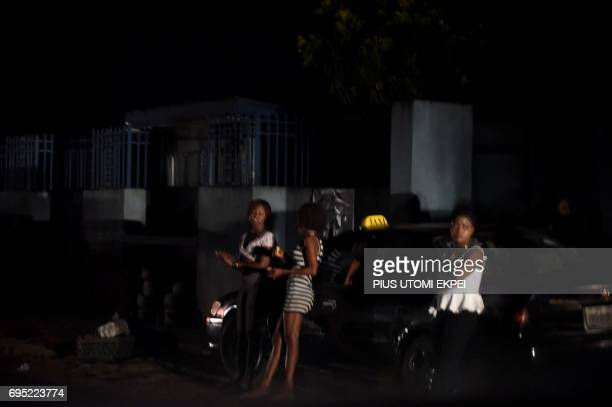 Prostitutes stand on the street in Benin City capital of Edo State southern Nigeria on March 29 2017 In Benin City Nigeria's capital of illegal...
