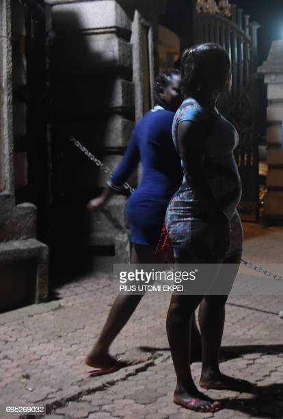 Prostitutes stand walk on the street in Benin City capital of Edo State southern Nigeria on March 29 2017 In Benin City Nigeria's capital of illegal...