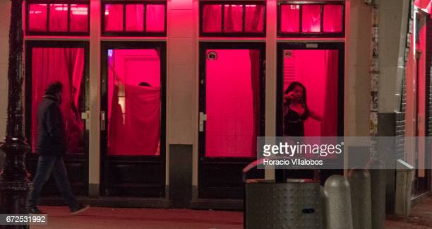 Prostitutes wait for clients behind glass doors in the Red Light District on April 19 2017 in Amsterdam Netherlands Prostitution has been legal in...