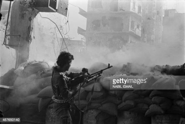ProSyrian militiaman from Lebanese Alawite Arab Democratic Party fires a machinegun as he fights 01 October 1985 in Tripoli northern Lebanon against...