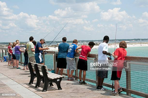 A Protect Florida's Ocean's T shirt worn by a young man fishing off the pier at Navarre Beach Florida USA