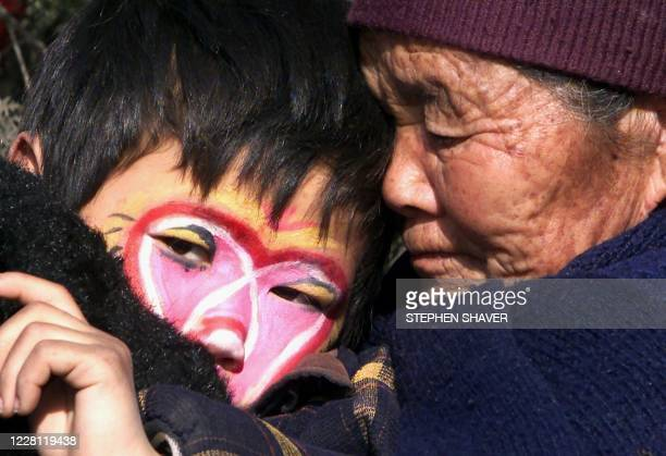 Protected against the winter chill by his grandmother's embrace, a young performer watches other traditional Chinese dance troupes perform at a...
