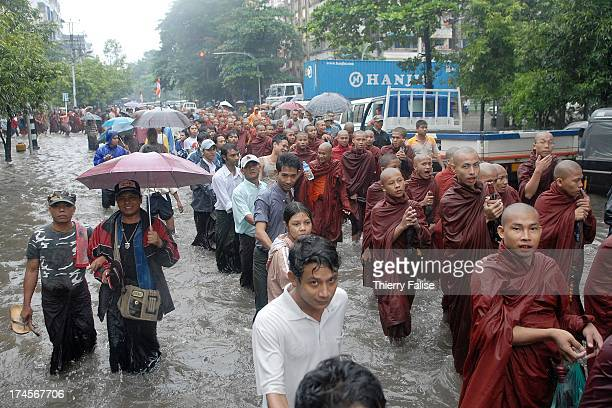 Protected by a human chain of civilian supporters Burmese Buddhist monks protesting against the military junta are marching in a street of Rangoon...