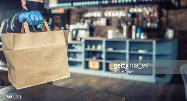 protected waiter giving a take away launch in a paper bag to customer at local restaurant. - bag stock pictures, royalty-free photos & images