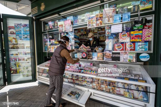 protected woman with a mask buys the press at a newsstand during the coronavirus pandemic. valencia, spain. - news stand stock pictures, royalty-free photos & images