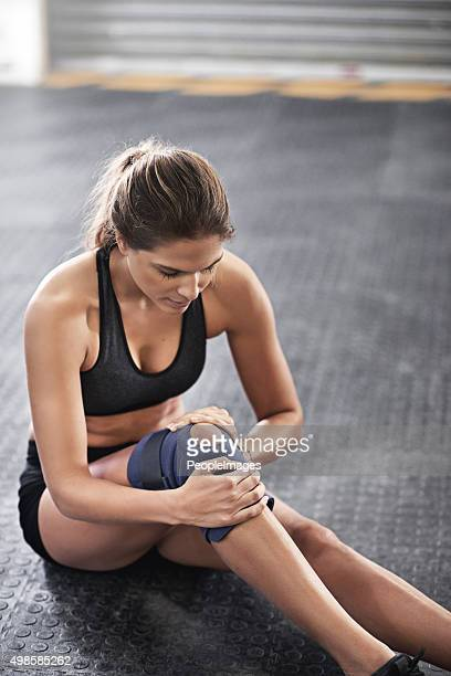 protecting her knee from further injury - human knee stock pictures, royalty-free photos & images