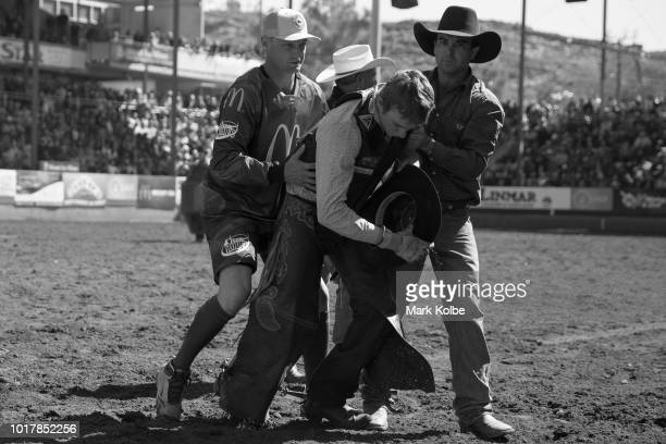 Protection athlete Brody Moss helps a fallen rider to safety during the Bull Ride competition of the 2018 Mount Isa Rotary Rodeo at the Buchanan Park...