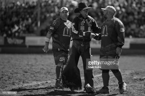 Protection athletes Darryl Chong and Lincoln Brown speak to bull rider Bryden Atkins after he feel during the Bull Ride competition of the 2018 Mount...