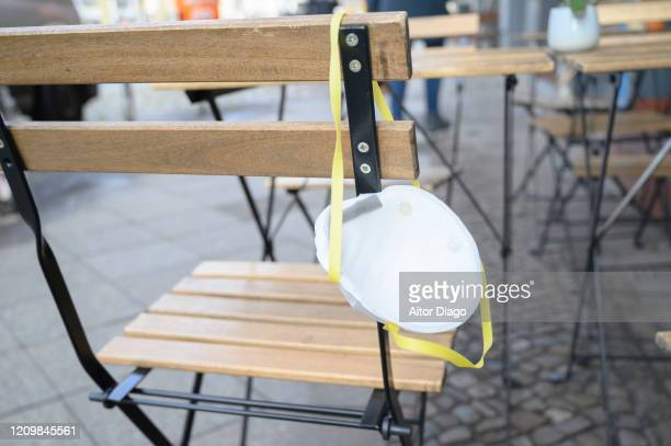 protection mask hanging on a chair. berlin, germany. - coronavirus winter stock pictures, royalty-free photos & images