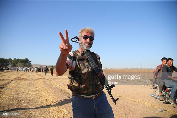 Protection of the Kurdish People fighters holds AK47's and flash Vsigns in the TurkishSyrian border after refugees and Turkish protestors pull down a...