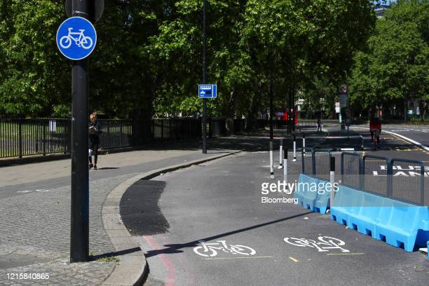 Protective barriers stand in a new bicycle lane created by Transport for London on Park Lane in London, U.K., on Thursday, May 28, 2020. To get...