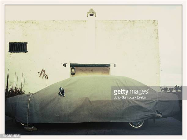 Protective covering over car against wall